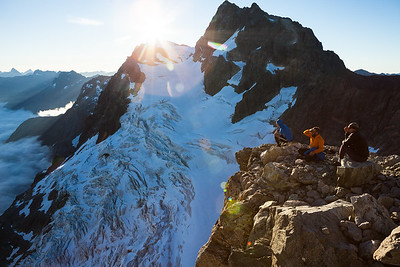 Three climbers sit above Donne Valley and opposite Taoka Icefall and Mount Patuki