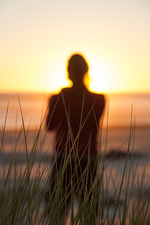 A man standing alone on a beach looking out towards the sea and the setting sun, Heaphy Beach, Kahurangi National Park