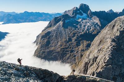 Mountaineer descending Mt Tarewai above Cleft Creek, Darran Mountains, Fiordland National Park, New Zealand