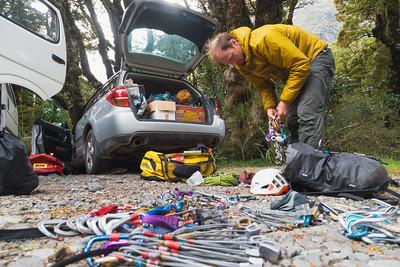 A male climber preparing climbing equipment beside the boot of a car, Homer Hut, Hollyford Valley, Darran Mountains, Fiordland National Park, New Zealand