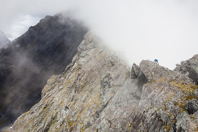 Climber scrambles on Homer Saddle, Moirs Mate, Fiordland National Park