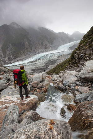 Tramper stands in stream bed above Franz Josef Glacier, Westland Tai Poutini National Park