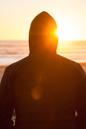 A man in silhouette standing alone on a beach looking out towards the sea and the setting sun, Heaphy Beach, Kahurangi National Park
