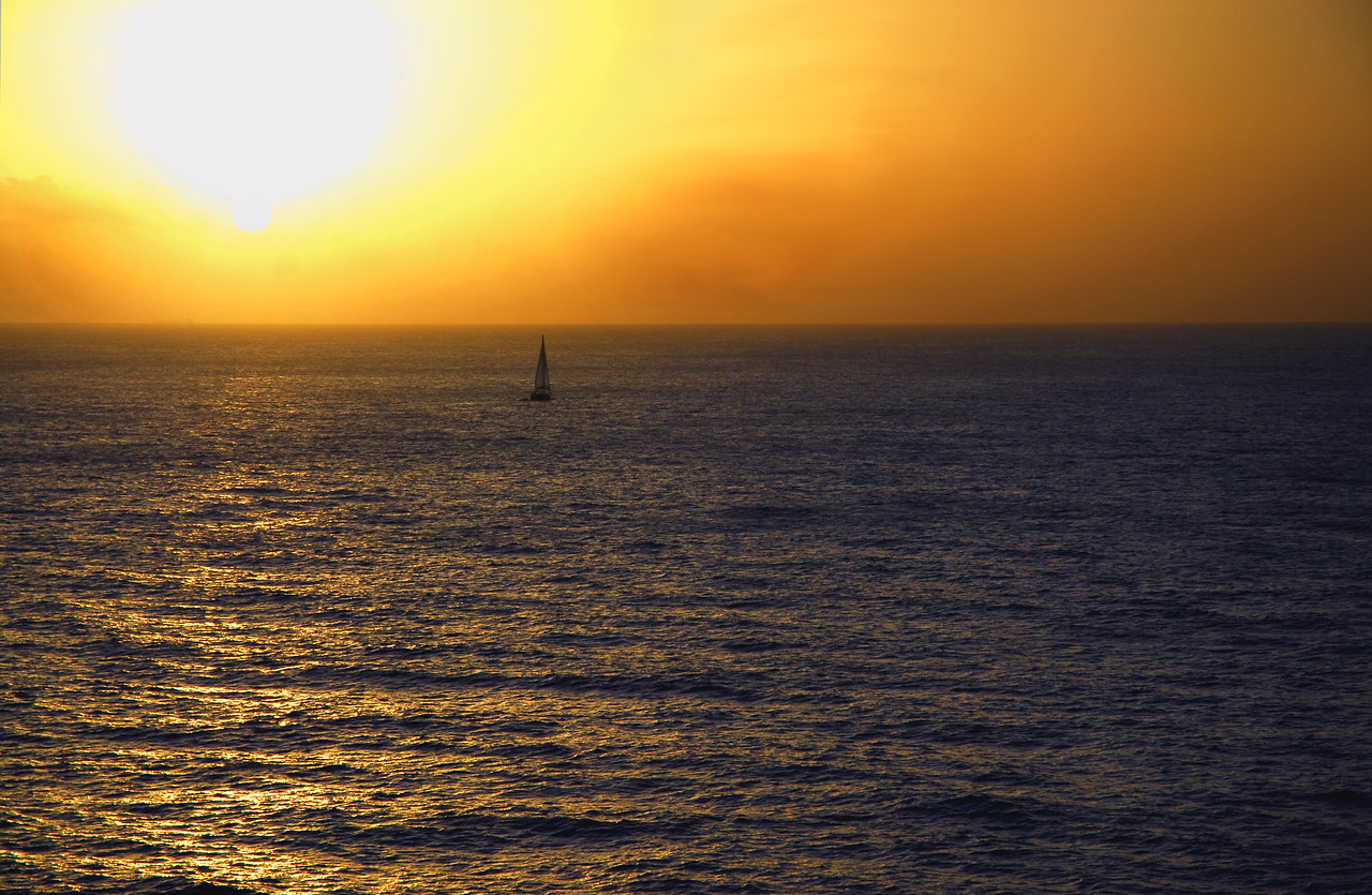 A sailboat sails into the amber cast sunset of the Carribean Sea