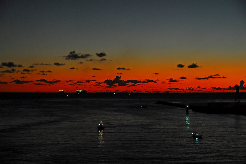 Just before dawn shore police and tugboats line up to receive the cruise ships returning to port after a week long Caribbean cruise