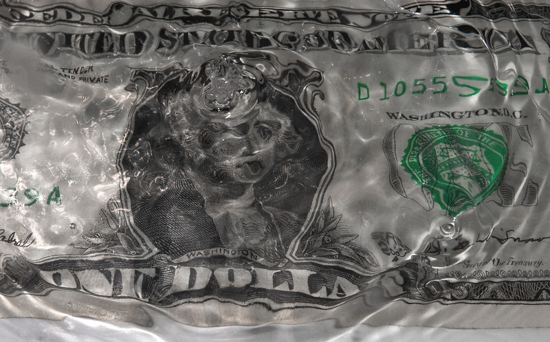 This is the image of George Washington on a One Dollar bill after a splash... the image of George looks as though he is sticking his tongue out