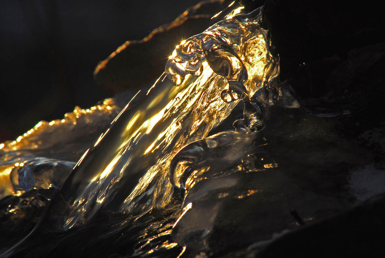 As the sunset one cold evening sun's rays refracted through the ice and water flowing over the ice creating this interesting photograph