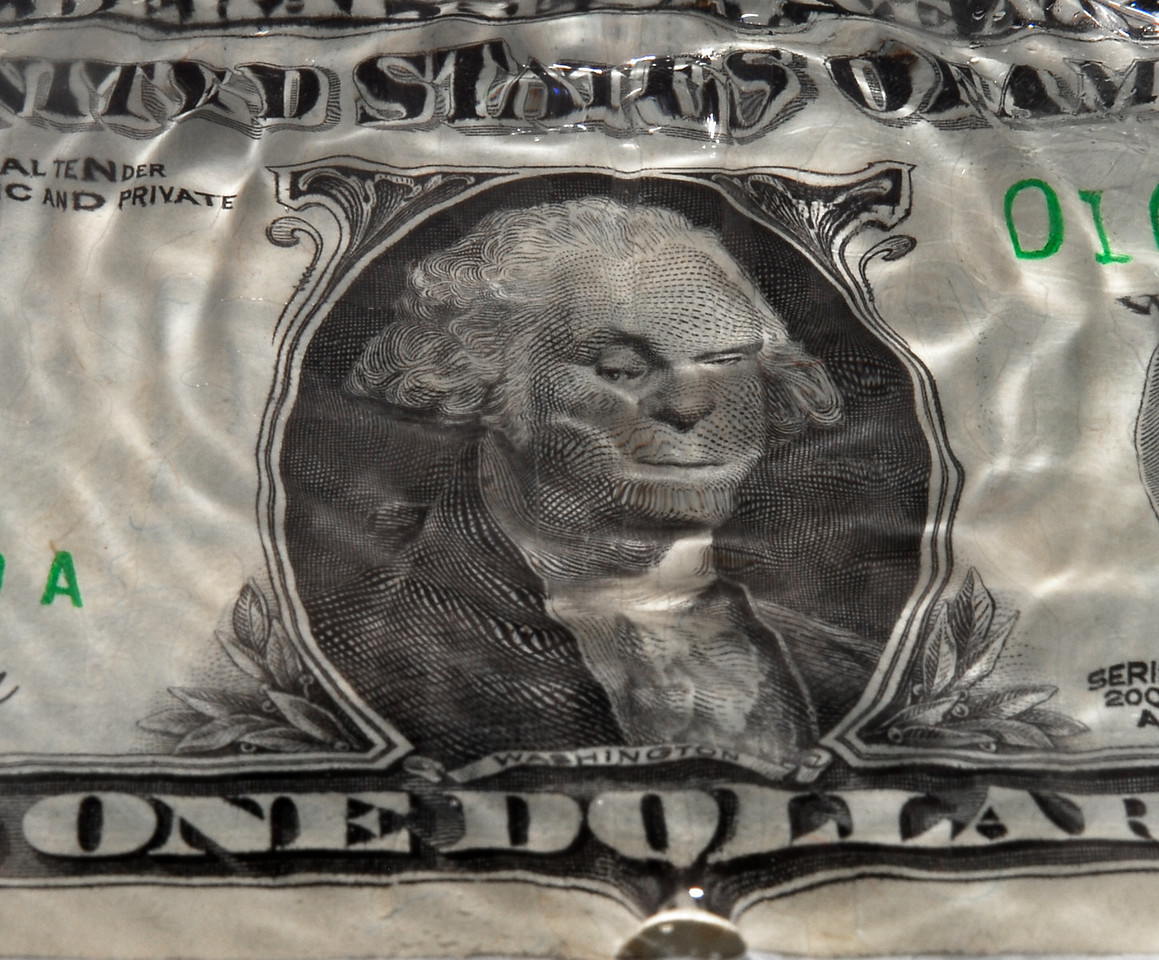 The ripples after a splash create the image of George Washington with a suspicious look on this one dollar photograph