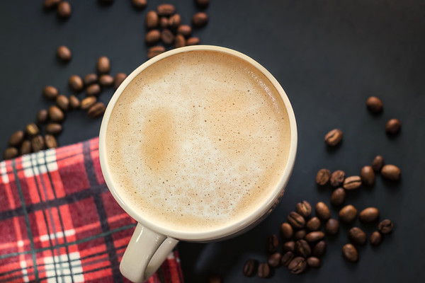 Overhead Angle of Cup of coffee and coffee beans on a Black Table