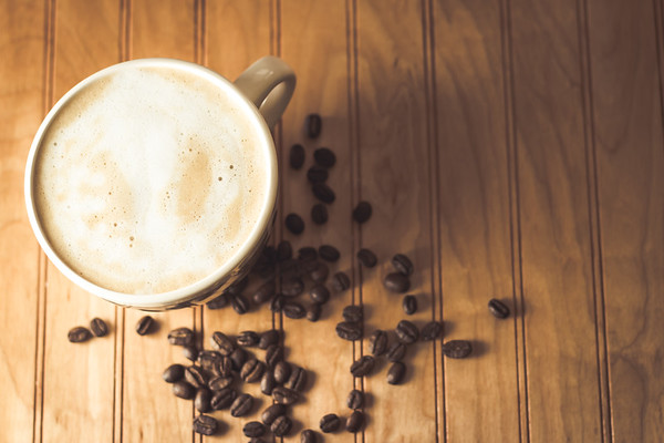 Overhead Angle of a Cup of coffee and coffee beans on a Wooden Table