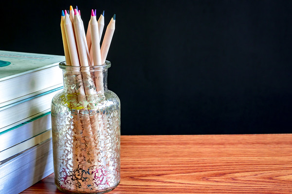Colored Pencils and Books on a Desk with A Chalkboard