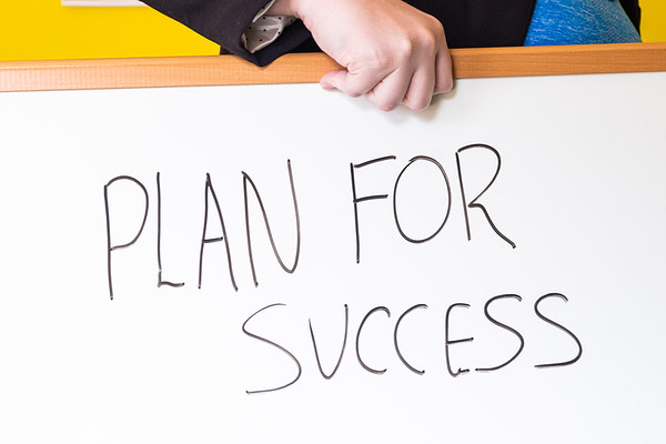 Person Holding a Whiteboard with Text Plan For Success