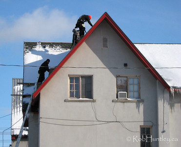 Winter roof repairs. All Saints Church in the community of Westboro in Ottawa, Ontario. Check the worker's shadow on the left side of the roof.