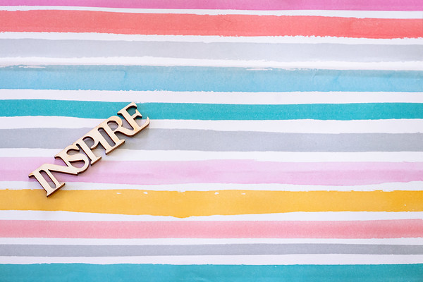 Overhead Angle of a Desk with the Word Inspire on a Colorful Pastel Background