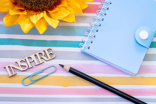 Overhead Angle of Notebook and Pencil on a Desk with the Word Inspire on a Colorful Pastel Background