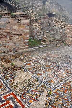 The Roman ruins at Ephesus, Turkey. Mosaic tiles decorated the floor of colonnaded galleries located in front of shops. A roof above the galleries protected pedestrians from sun or rain and supported terraced houses used by rich Ephesians. Curetes Street.
