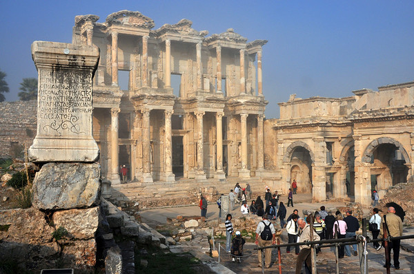 The Roman ruins at Ephesus, Turkey. The Celsus Library, shown here, was built in AD 114 – 117 by Consul Gaius Julius Aquila as a mausoleum for his father, Julius Celsus Polemaeanus, who is buried in a in a tomb under the apsidal wall on the right side of the back wall. The library was one of the wealthiest in the empire and at its peak had more than 12,000 scrolls. The statutes seen in the niches between the doors symbolized wisdom, Sophia, Knowledge ( episteme ), intelligence ( ennoia ) and virtue (arte) of Celsus