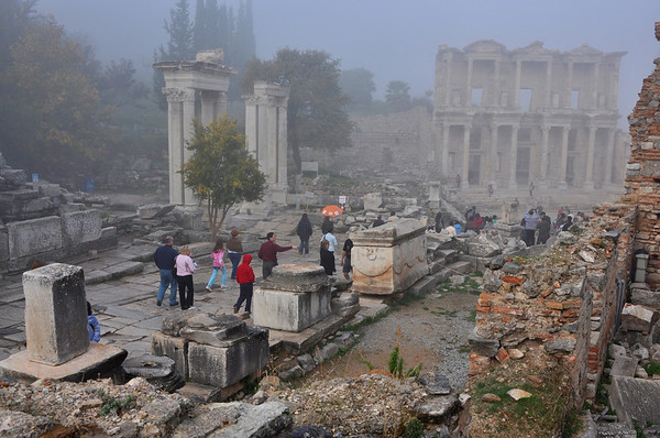 The Roman ruins at Ephesus, Turkey. Visitors head down Curetes Street, past Hadrian's Gate on the left, and towards the Celsus library (right, in fog).