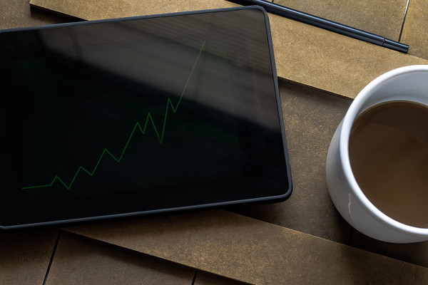 Overhead View of an Upward Green Graph on a Tablet and Coffee