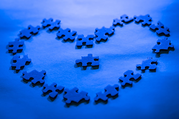Blue Puzzle Pieces in the Shape of a Heart on a Blue Background