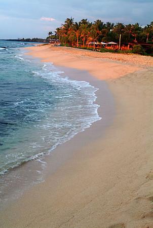 Last rays of the setting sun illuminate Hualalai resort beach and restaurant, Big Island of Hawaii
