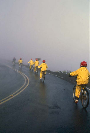 Bicycling down the outer slopes of Haleakala volcano in the early morning fog, Maui.