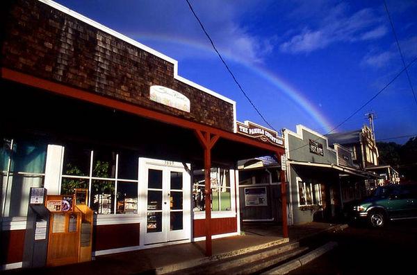 A rainbow and moon hang over the historic cowboy town of Makawao on the pastoral slopes of Haleakala volcano, Maui.