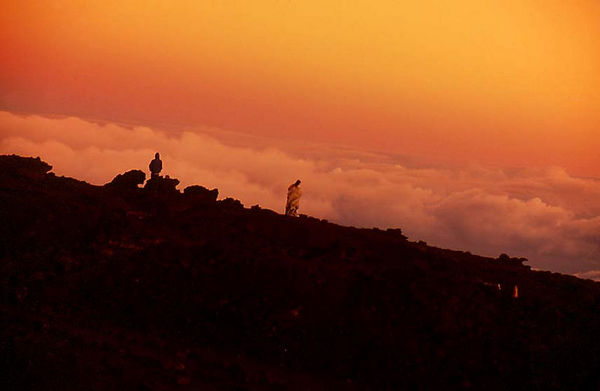 Spectators watch sunrise at the top of Haleakala volcano, Maui.