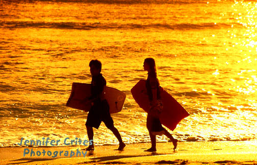 carrying bodyboards at sunset, Waikiki Beach