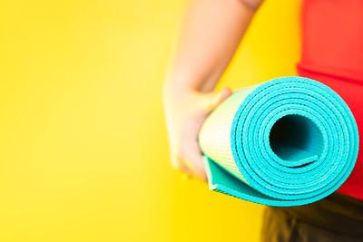 Woman Holding a Blue Yoga Mat