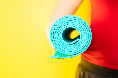 Woman Holding a Blue Yoga Mat