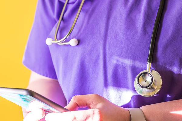 Woman Doctor Wearing Purple Scrubs and a Stethoscope using a cellphone