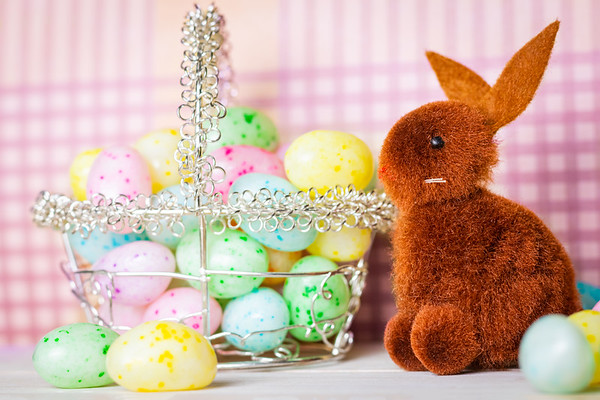 Brown Easter Bunny and a Basket of Colorful Jelly Beans on a Pink Background
