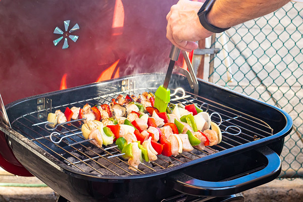 Man Basting Chicken Kebabs On the Barbecue Grill