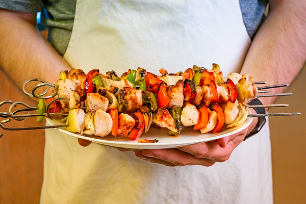 Man Holding a Plate of Shish Kebabs On Skewers