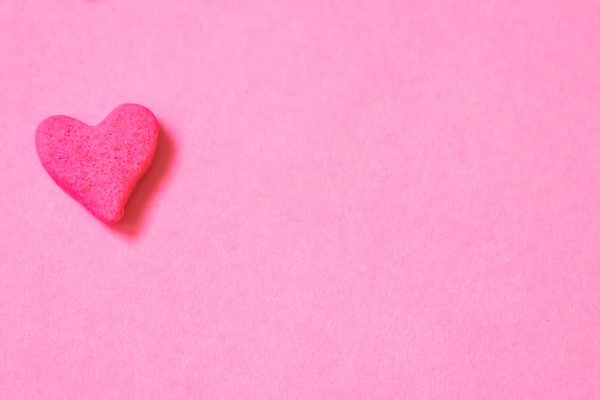 One Pink Candy Heart on a Pink Background