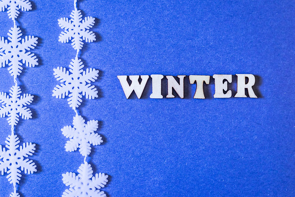 Winter Text on a Blue Background with white Snowflakes
