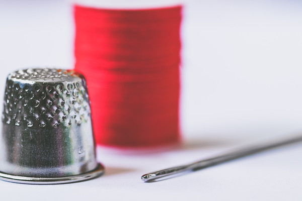 Red Thread, Silver Thimble and Sewing Needle on a White Background