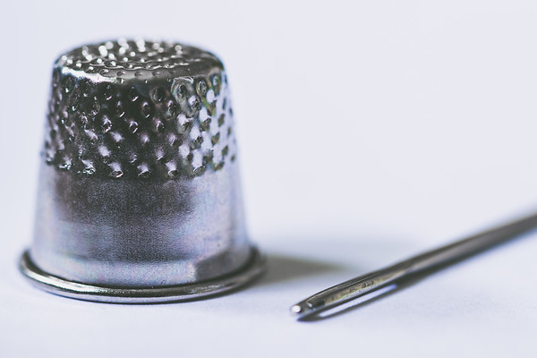 Silver Thimble and Sewing Needle on a White Background