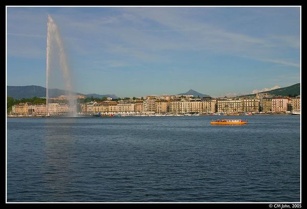 "<H2><b>Geneva</b></H2> <P ALIGN=LEFT>The ""Rade"" in Geneva, and its most characteristic features: the ""jet d'eau"", and the banks in the background! The red and gold boat is a Geneva ""Mouette"" (mew), part of the (touristic) public transportation system.</P>"