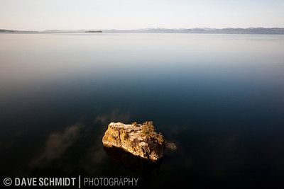 This image took a couple years to make.  I had taken a similar shot with a point-n-shoot I carried when running and took a similar shot.  From that shot I knew I had to go back and take it properly.  The challenge is there is only a couple days a year where you can take this shot.  The calmness of the water is pretty rare on Lake Champlain as well as a lack of boats.  This photo is taken in March, 2009 using a tripod, a neutral density filter and a long exposure so further soften the water.  The white area next to the rock is the reflection of a cloud. The place is Lone Tree Point, just north of North Beach in Burlington.  The land is owned by the Catholic Church (or was) and it's a quick hike from the State Park.  The cliff is extraordinary and this rock sits just off-shore.  The mountains you see are the western Adirondacks in New York.  Burlington, Vermont.  March, 2009.