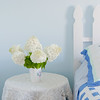 Bouquet of white hydrangea flowers on a site bed table in a country bedroom.