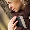 beautiful woman with book leaning on a tree