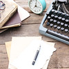 Vintage black typewriter on wooden table, outdoors