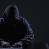 Slow Pan Across Hacker at Keyboard Wearing Hoodie