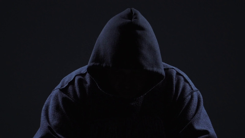 Hacker Wearing Hoodie Lifts Head