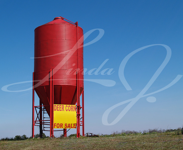 Small red grain silo used to sell corn for deer with copy space.