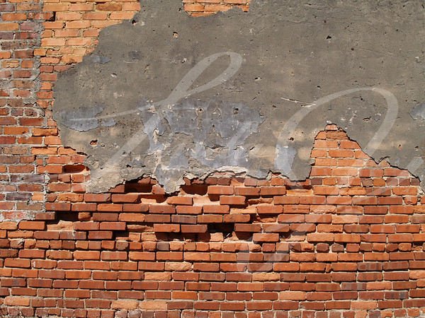 Old weathered wall with red multi-sized brick and a patched area.