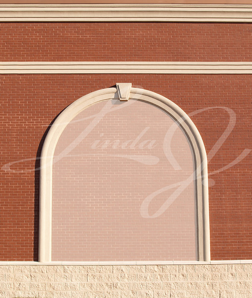Ornate Roman styled brick wall with curved molding and a reduced opacity brick copy space.