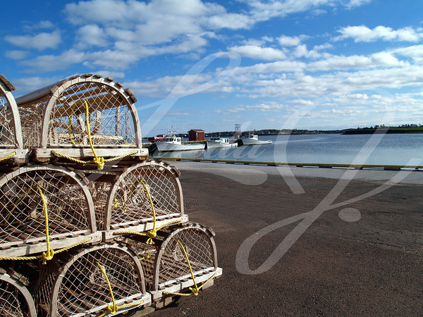 Lobster traps stacked on the wharf with fishing boats and harbor in the background and space for copy.